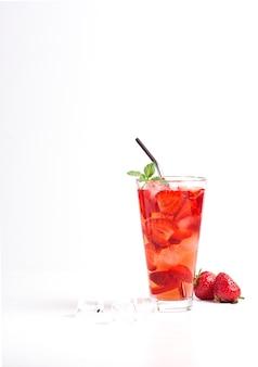 Limonata rinfrescante alla fragola con fragole, limone, menta, soda e ghiaccio in un bicchiere