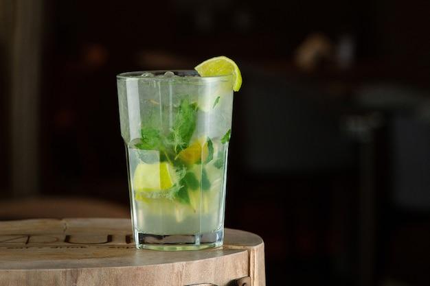 Mojito cocktail estivo rinfrescante con ghiaccio, menta fresca e lime. cocktail mojito su uno sfondo scuro. supporto in legno.