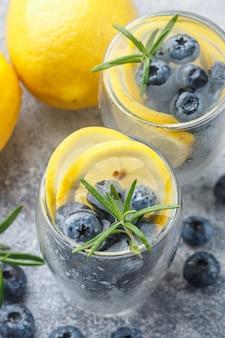 Bevanda estiva rinfrescante con limone, mirtilli, rosmarino e cubetti di ghiaccio. detox, limonata, cocktail. messa a fuoco selettiva