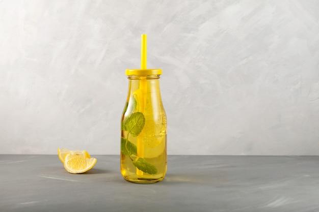 Bevanda estiva rinfrescante con miele di limone e menta bottiglia di vetro trasparente gialla sul tavolo grigio