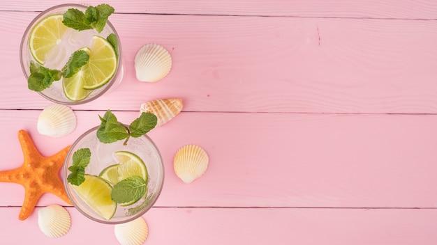 Una bevanda estiva rinfrescante con mojito lime e menta si erge su un tavolo rosa. vista dall'alto, copia dello spazio.
