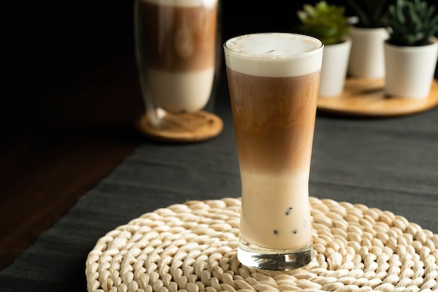 Bevande o bevande estive rinfrescanti, si compone di tre strati, latte freddo, caffè e latte schiumato freddo in un bicchiere alto, su tovaglietta intrecciata, tovaglietta grigia, tavolo in legno marrone scuro.