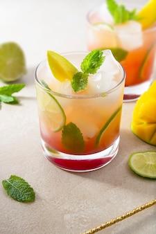 Cocktail rosa estivo rinfrescante a base di succo di mango fresco, cubetti di ghiaccio e foglie di menta.