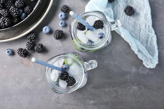 Acqua rinfrescante con more e mirtilli in barattoli di vetro sul tavolo