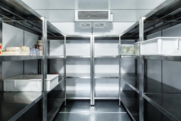 Camera del frigorifero con ripiani in acciaio in un ristorante da vicino