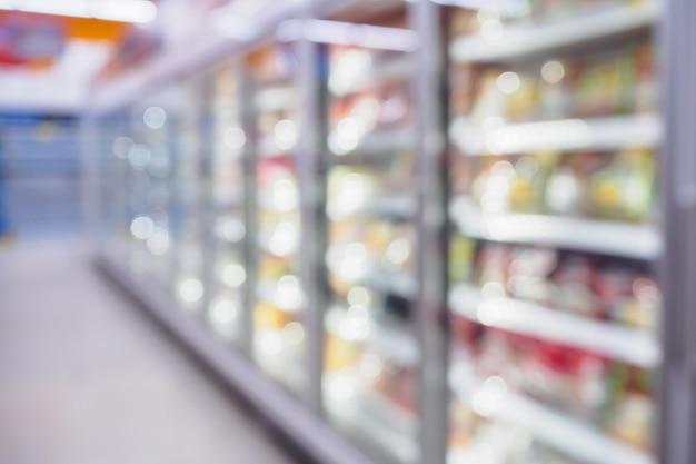 Ripiani del frigorifero nel supermercato sfondo sfocato
