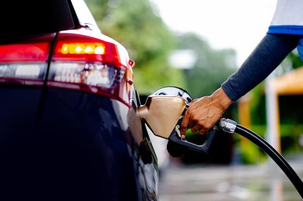 Rifornisci la tua auto al distributore di benzina con le tue mani. per un viaggio snello nella guida lungo il tragitto