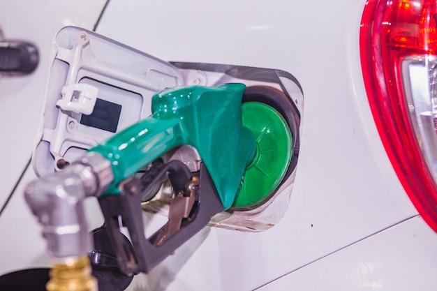 Rifornimento di carburante riempire l'auto con benzina a benzina alla stazione di servizio e pompa di benzina che riempie l'ugello del carburante nel serbatoio del carburante dell'auto