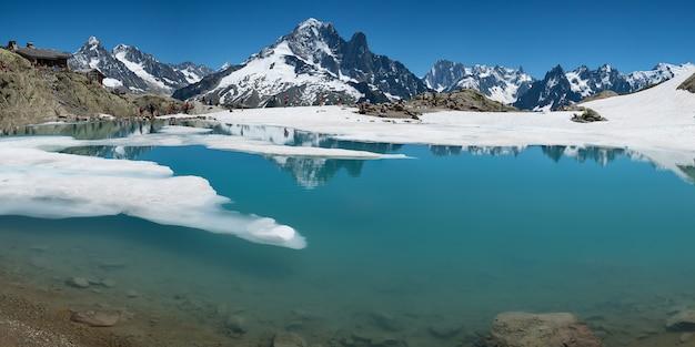 Rifugio in alta montagna con lago in disgelo di fronte al monte bianco nelle alpi