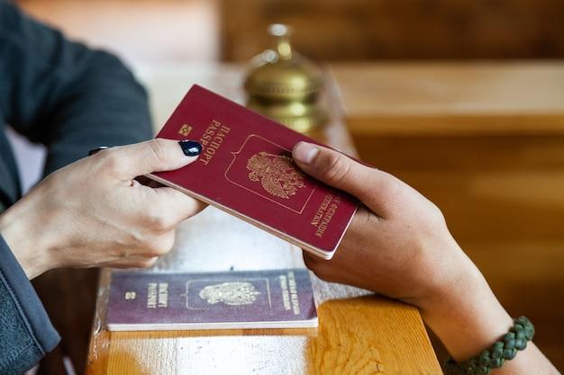 Registrazione dei turisti in hotel, passaporto alla reception in legno
