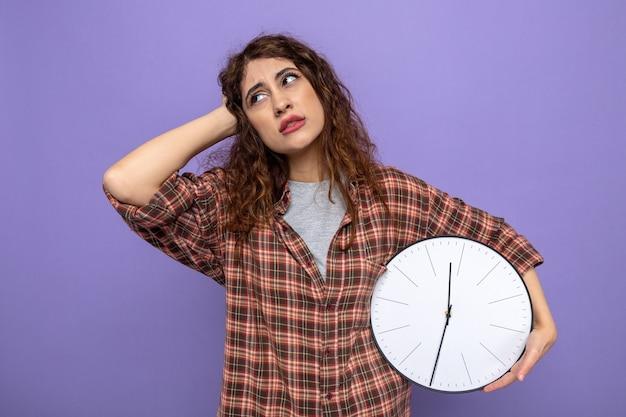 Deplorato di aver messo la mano sulla testa giovane donna delle pulizie che tiene l'orologio da parete isolato sul muro viola