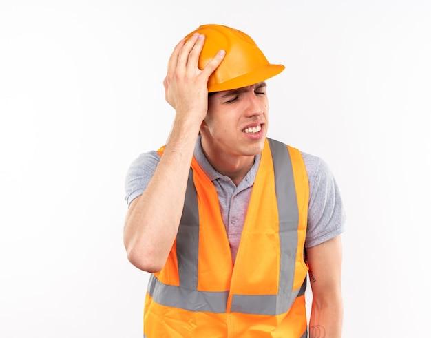 Deplorato con gli occhi chiusi giovane costruttore in uniforme che mette mano sulla testa isolata sul muro bianco