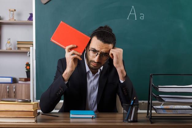 Deplorato con la testa abbassata insegnante maschio con gli occhiali che tiene il libro seduto al tavolo con gli strumenti della scuola in aula