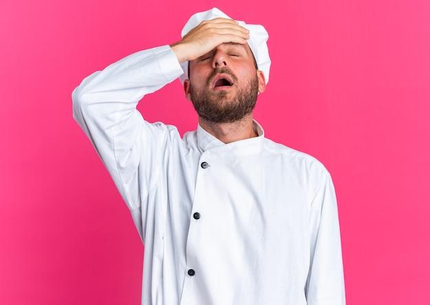 Rimpiangendo il giovane maschio caucasico cuoco in uniforme da chef e berretto che tiene la mano sulla fronte con gli occhi chiusi isolati sul muro rosa