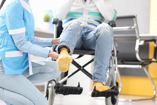 Medico di riabilitazione che aiuta a sollevare la gamba del paziente in sedia a rotelle. recupero dal concetto di lesioni