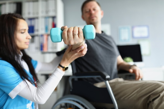 Terapista della riabilitazione che aiuta l'uomo disabile in sedia a rotelle a sollevare il manubrio in primo piano. riabilitazione dei pazienti dopo il concetto di trauma