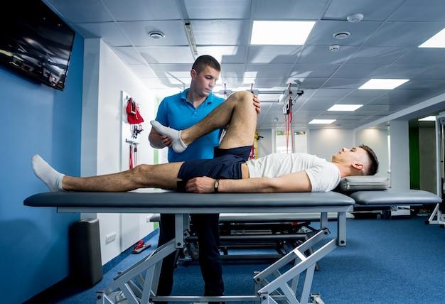 Terapia riabilitativa. fisioterapista che lavora con un giovane paziente maschio nel centro di riabilitazione