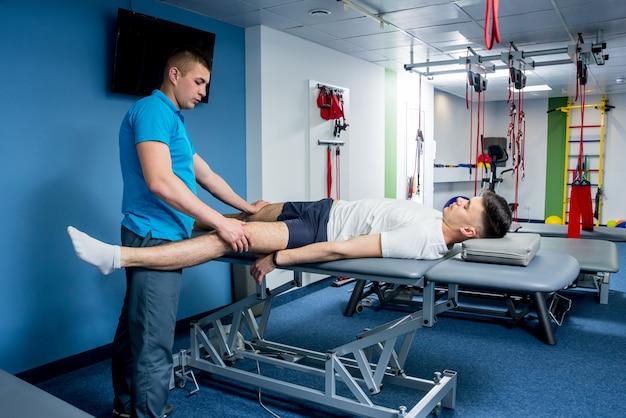 Terapia riabilitativa. fisioterapista che lavora con un giovane paziente maschio