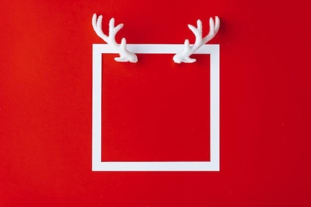 Corna di renna con cornice bianca su fondo rosso