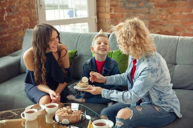Gioia. madre, figlio e sorella a casa si divertono. vacanze, famiglia, comfort, concetto accogliente, festeggiare il compleanno. bella famiglia caucasica. trascorrere del tempo insieme, giocare, ridere, salutare