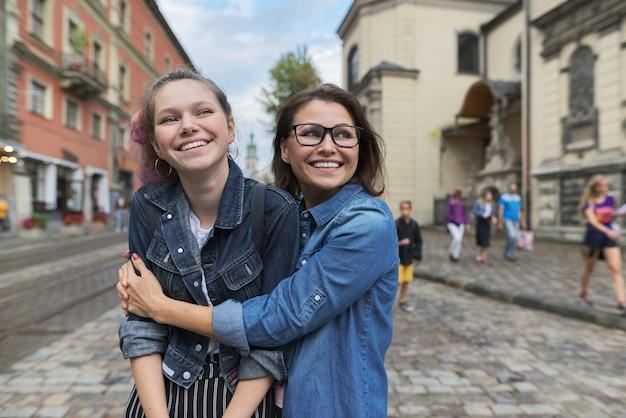 Genitore e adolescente di relazione, abbracciando madre e figlia sorridenti