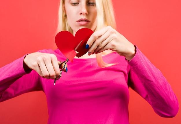 Problemi di relazione. rottura. ragazza con il cuore spezzato. l'amore fa male. rottura delle relazioni. amore infelice. la ragazza taglia il cuore.