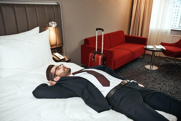 Rilassati dopo un lungo viaggio di lavoro. uomo d'affari in giacca e cravatta seduto con lo smartphone sul letto in una camera d'albergo e chiacchierando con un amico