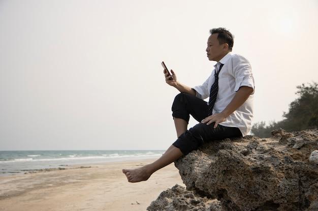 Rilassati uomo d'affari asiatico in un panno casual seduto su una scogliera in spiaggia con meno teso o ansioso alla fine della giornata in possesso di smartphone mobile che collega le persone sui social network alla fine della giornata
