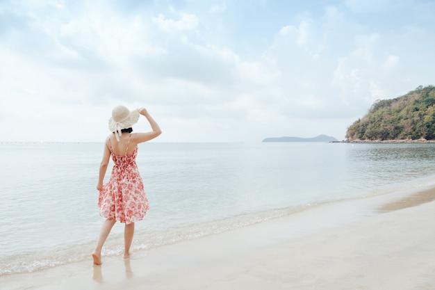 Rilassi la donna sul cielo della spiaggia e delle nuvole.
