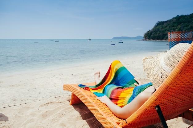 Rilassi la donna sulla sdraio sulla spiaggia e sul cielo delle nuvole.