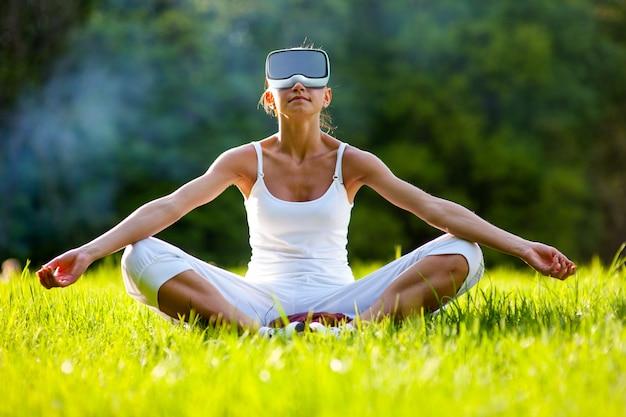 Rilassi la ragazza di zen che usando i vetri della cuffia avricolare di realtà virtuale che si siedono sulla via