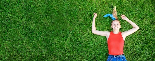 Concetto di rilassamento e meditazione. la giovane ragazza bionda si trova sull'erba verde esamina la macchina fotografica fuori nel parco.