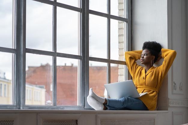 Donna africana rilassata che si siede sul davanzale della finestra