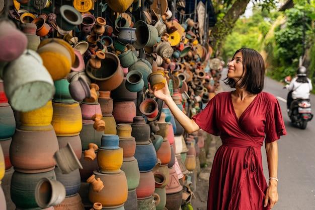 Atmosfera rilassata. felice ragazza bruna che prova felicità mentre sceglie il regalo per i suoi amici dal suo viaggio