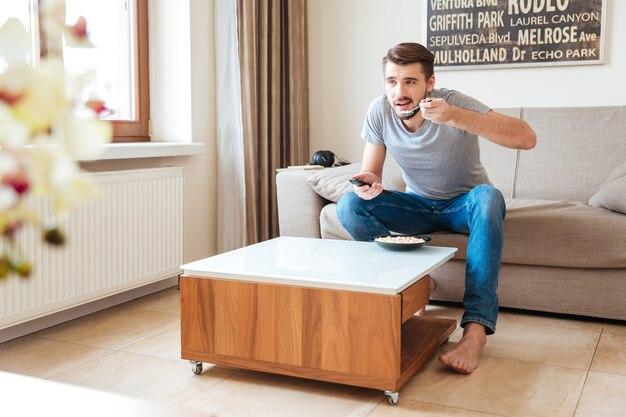Giovane attraente rilassato che usa il telecomando e mangia cereali sul divano in camera