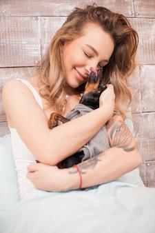 La bella donna rilassata in pigiama abbraccia il suo cagnolino a letto di notte.