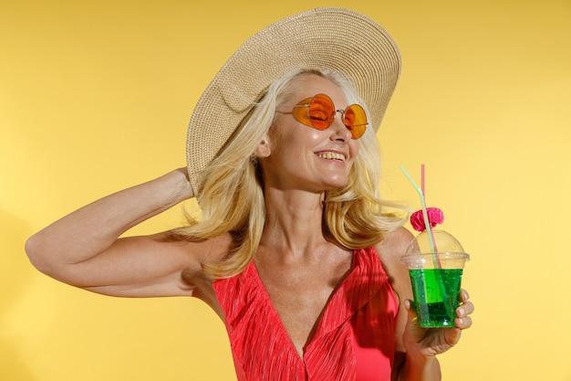 Donna bionda rilassata in costume da bagno rosso occhiali da sole e cappello di paglia che sorride con la regolazione degli occhi chiusi