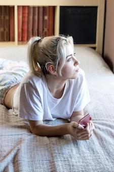 Giovane donna bionda rilassata sdraiata sul letto mentre si tiene un telefono cellulare