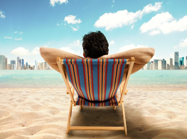 L'uomo d'affari rilassato sulla sedia a sdraio al mare guarda la città