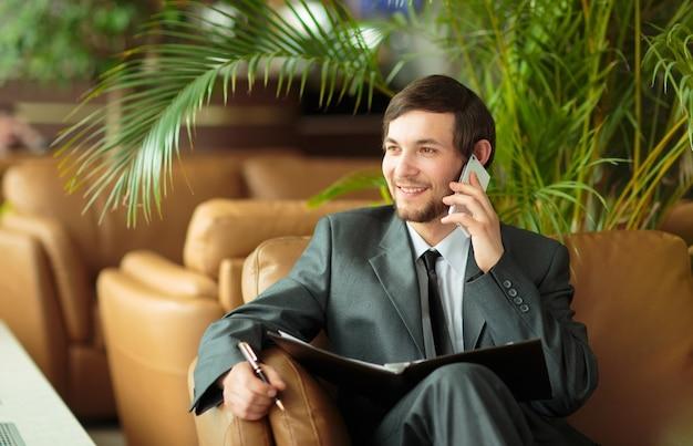 Uomo d'affari rilassato seduto davanti alle finestre dell'ufficio