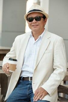 Uomo d'affari rilassato con caffè all'aperto