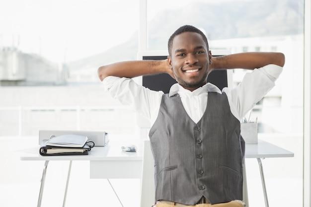 Uomo d'affari rilassato con le mani dietro la testa