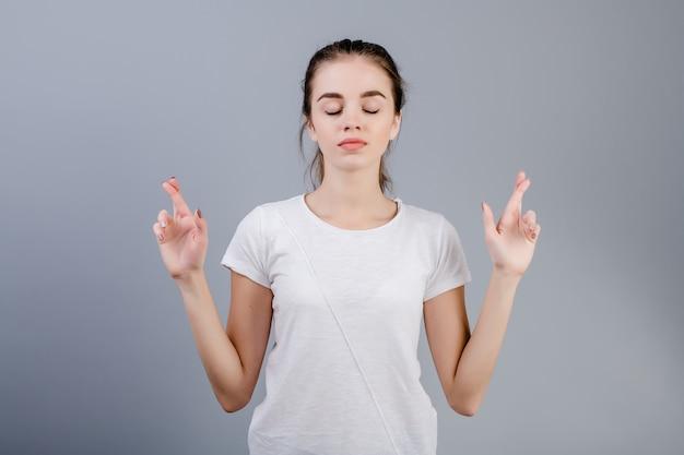 Le dita preganti calme rilassate della tenuta della giovane donna hanno attraversato isolato sopra grey