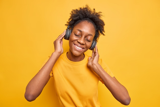 Rilassata spensierata ragazza millenaria afro americana inclina la testa tiene le mani sulle cuffie stereo keeps
