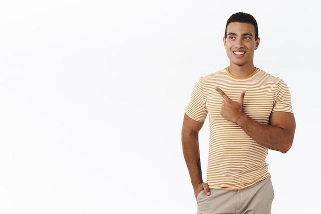 Ragazzo maschile rilassato e casual in piedi su uno sfondo bianco vicino a uno spazio bianco vuoto chiaro