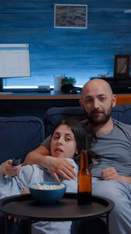 Coppia rilassata a casa seduta sul divano a guardare programmi tv e mangiare popcorn e bere birra, cambiare canale