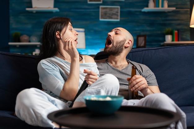 Coppia rilassata seduta sul divano a guardare film in televisione, bere birra giocando a giochi di popcorn godendosi il tempo insieme a casa per il tempo libero, la felicità e il concetto di persone sposate.