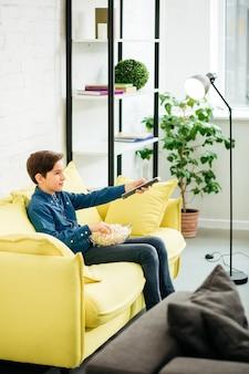 Adolescente felice rilassato seduto sul divano e allungando il braccio mentre cambia canale con telecomando e mangia popcorn