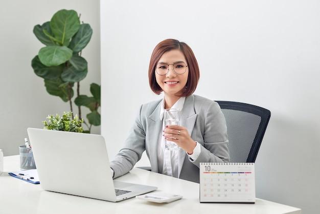 Donna di affari matura rilassata che tiene bicchiere d'acqua e lavora al suo computer portatile in ufficio