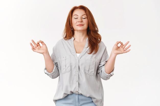 Rilassata di mezza età spensierata donna rossa esercizio yoga respirazione pratica raccogliere pazienza rilasciare stress sorridere chiudere gli occhi inspirare aria fresca in piedi loto nirvana zen posa meditare felicemente